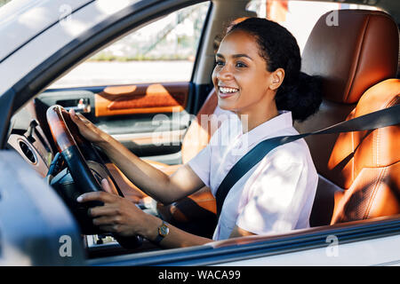 Smiling woman driving looking out a car window. Happy woman holding a steering wheel in the vehicle. - Stock Photo
