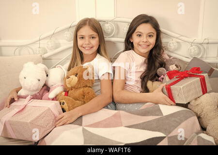 Merry Christmas and Happy New Year. Cute little girls with presents in bed. Opening presents. New Year surprise. Happy little children hold gift boxes. Make the moments special this Christmas morning. - Stock Photo