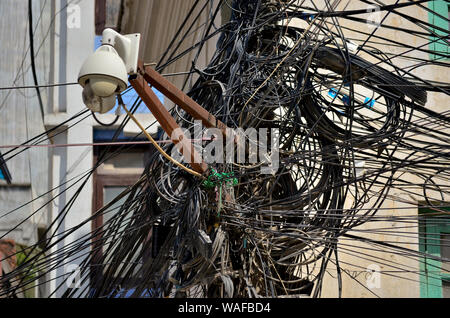 Big tangle of dirty black wires in Kathmandu, Nepal - Stock Photo
