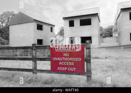 Imber open day for visitors to see the deserted ghost village on Salisbury Plain, Wiltshire UK in August - Danger warning sign, infrared effect - Stock Photo