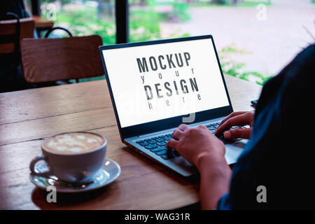 Mockup image of a business woman using and typing on laptop computer keyboard with blank white desktop screen with coffee latte cup on wooden table. - Stock Photo
