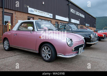 1991 Pink Retro-style Nissan Figaro 2 Door Fixed Profile Convertible White Roof front drivers side offside view Japanese City Car parked Holy Loch Mar - Stock Photo