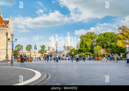 Matthias Square with the Matthias Church and the Fisherman's Bastion with tourists enjoying the sunny day in Budapest Hungary - Stock Photo