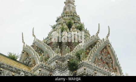 weeds growing on an outer prang of wat arun temple in bangkok - Stock Photo