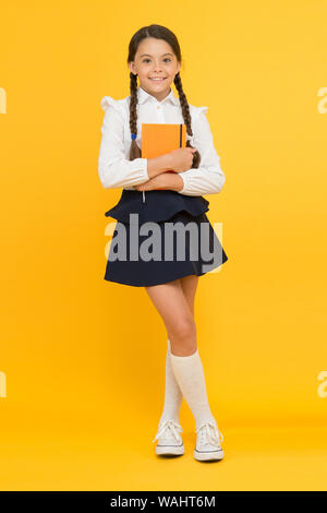 School girl formal uniform hold book. School lesson. Study literature. Towards knowledge. Learn following rules. Welcome back to school. Inspirational quotes motivate kids for academic year ahead. - Stock Photo