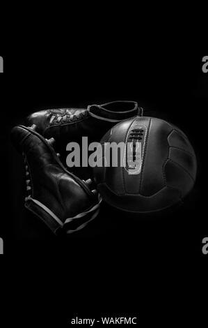 Antique leather football soccer ball and vintage cleats, boots, football shoes against a black background in black and white B&W - Stock Photo