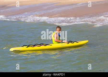 Lifeguard with surf board at Branksome Chine, Poole, Dorset UK on a warm sunny day in August - Stock Photo