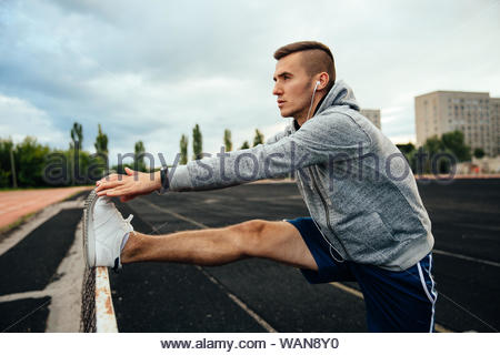 Close-up profile of a young handsome man doing exercises, working out legs, listening to music in headphones, dressed in sportswear, at the stadium - Stock Photo