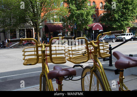 Saratoga Springs, New York State: August 4, 2019 - Two Golden Bicycles facing Broadway Street in front Adelphi Hotel, Downtown Saratoga Springs - Stock Photo