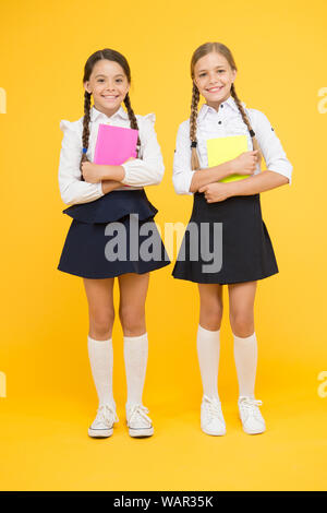 School friendship. Schoolgirls wear school uniform. Knowledge day. School day. Girl with copy books or workbooks. Study together. Kids cute students. Schoolgirls best friends excellent pupils. - Stock Photo