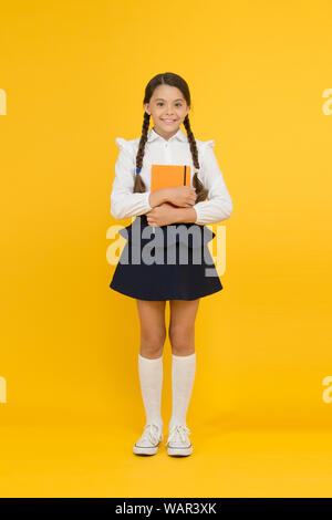 Inspirational quotes motivate kids for academic year ahead. School girl formal uniform hold book. School lesson. Study literature. Towards knowledge. Learn following rules. Welcome back to school. - Stock Photo