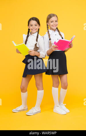 Knowledge day. School day. School friendship. Girl with copy books or workbooks. Study together. Kids cute students. Schoolgirls best friends excellent pupils. Schoolgirls wear school uniform. - Stock Photo
