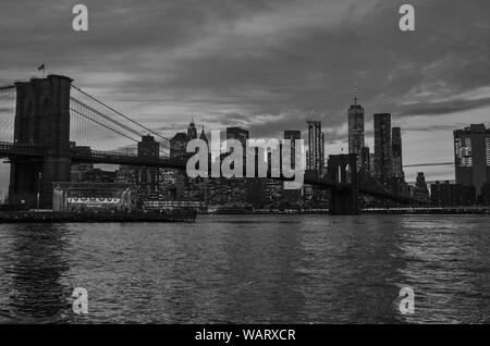 Black and white photo of the Brooklyn Bridge during a cloudy sunset in foreground with New York City skyline in background. - Stock Photo