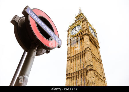 London, UK - 5th June 2017: The houses of Parliament clock tower, Big Ben, with a London Underground sign in the foreground, against white sky backgro - Stock Photo