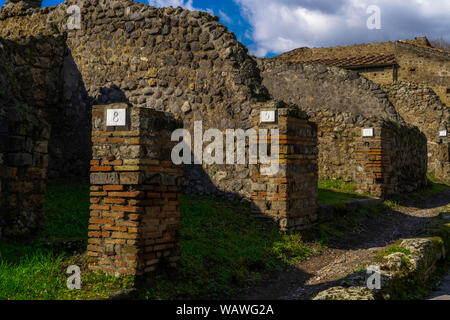 Pompeii, Italy Roman architecture city block remains with numbered homes entrances. Numbers in doorways identifying stone houses ruins, insula. - Stock Photo