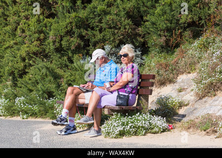 Branksome Chine, Poole, Dorset UK. 22nd Aug 2019. UK weather: a lovely warm sunny day as beachgoers head to the seaside at Branksome Chine beach to enjoy the sunshine, as temperatures are set to get higher for the Bank Holiday weekend. Couple enjoy a rest and relax along the promenade. Credit: Carolyn Jenkins/Alamy Live News - Stock Photo
