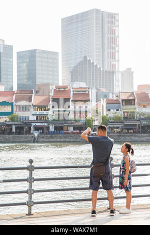 A pair of tourists - father stopped to take picture of the scenic Singapore River while the daughter looked on. Singapore, Southeast Asia - Stock Photo