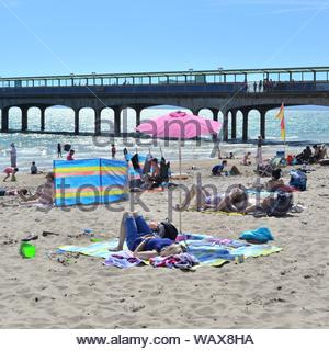 Boscombe, Bournemouth, Dorset, England, UK. 22nd Aug, 2019. Weather: Warm and sunny afternoon on the south coast beach with temperatures rising into the bank holiday weekend accompanied by a good dose of late summer hot sunshine. People on the beach enjoying the sun. Credit: Paul Biggins/Alamy Live News - Stock Photo