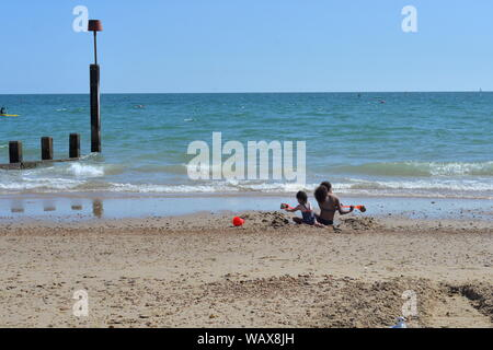 Boscombe, Bournemouth, Dorset, England, UK. 22nd Aug, 2019. Weather: Warm and sunny afternoon on the south coast beach with temperatures rising into the bank holiday weekend accompanied by a good dose of late summer hot sunshine. A mother and daughter play in the sand by the sea. Credit: Paul Biggins/Alamy Live News - Stock Photo
