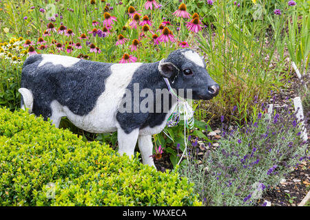 Cow ornament among the flowers at Patrick's Patch, Beaulieu, New Forest, Hampshire UK in August - Stock Photo
