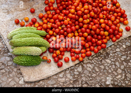 Fresh red tomatoes and green bitter gourd in Asian morning market. Organic homegrown argriculture products - Stock Photo