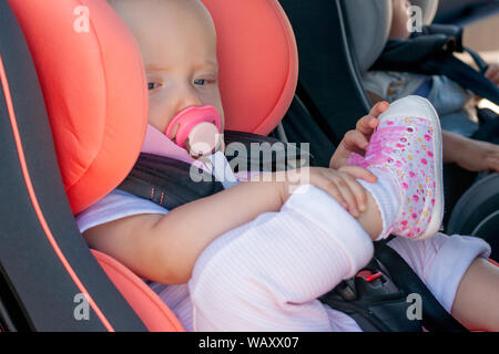 Twins boy and girl in child seats in the car. Safety transportation for babies. Children up to a year - Stock Photo