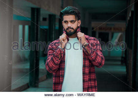 man wearing white shirt and red and black plaid collared button-up long-sleeved shirt standing - Stock Photo