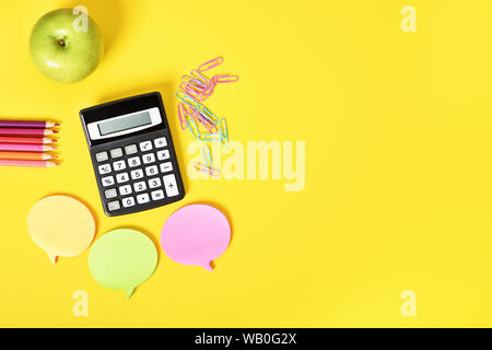 Math accessories for class. Flat lay of calculator, sticky notes and apple on yellow background. - Stock Photo