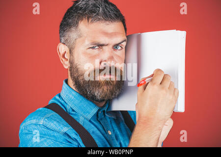brutal caucasian hipster with moustache. Mature hipster with beard. man. male with beard. Bearded brutal man. serious man making notes in notebook. se - Stock Photo