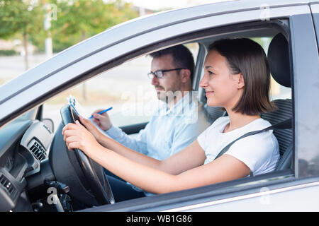 Instructor and young female student, driving lesson - Stock Photo