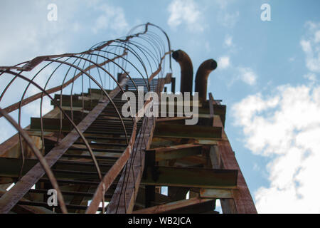 Bottom view of old rusty steps on metal tower, selective focus - Stock Photo