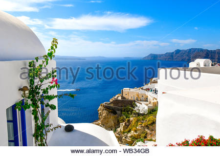 View of the Aegean Sea and caldera as a boat crosses, from the cliffside city of Oia, Greece, on the Cyclades island of Santorini - Stock Photo