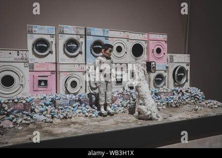 Boy and dog at laundromat in front of abandoned washing machines, on display in London at the Isle of Dogs exhibition, directed by Wes Anderson – Marc - Stock Photo