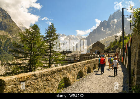Scenic mountain view with tourists heading to the rack railway station of Montenvers at the Mer de Glace above Chamonix-Mont-Blanc in summer, France - Stock Photo