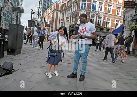 Young woman reaching for purse in handbag to make donation to young man fundraising for education in Liverpool Street London England UK  KATHY DEWITT - Stock Photo