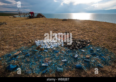 On the ground, stones are laid in the form of two swans and a heart overlooking Lake Baikal. Symbol of love. Black and white swan on a blue lake. The - Stock Photo