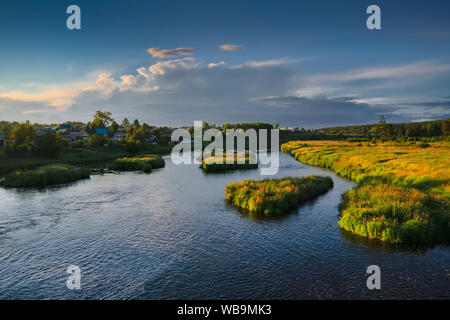 The Russian village on the banks of the river against the backdrop of the setting sun. - Stock Photo