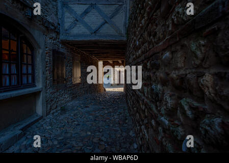 Dark passageway leading to a sunny street, taken at the end of a summer afternoon from a narrow alley, Perouges, France - Stock Photo