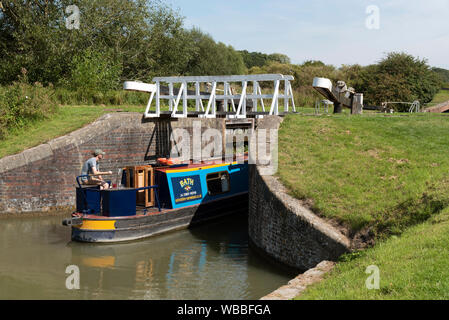 Devizes, Wiltshire, England, UK. August 2019. Narrowboat entering a lock on the Caen Hill flight of locks on the Kennet and Avon Canal. - Stock Photo