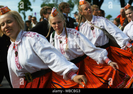 Tallinn, Estonia - 7.04.2009 - young women in Estonian traditional clothing  dancing at street parade for folk dance and folk song festival - Stock Photo