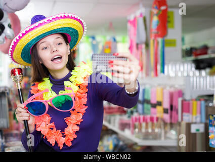 Comically dressed happy girl making funny selfies photo in festive accessories shop - Stock Photo