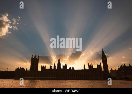 Dramatic sun beams behind the Palace of Westminster as the sun sets in London. - Stock Photo