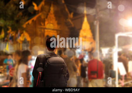 Male tourist sightseeing old temple ,traveling concept. Street photographer wandering on famous night walking street in chiengmai city, northern Thail - Stock Photo