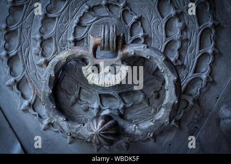 closeup of old rusty ornate door knocker on door - Stock Photo
