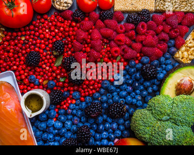 Clean eating concept over wooden background, top view. Variety of vegetables, fruit, seeds, bean, superfood,salmon fish, condiment for vegan, raw diet - Stock Photo