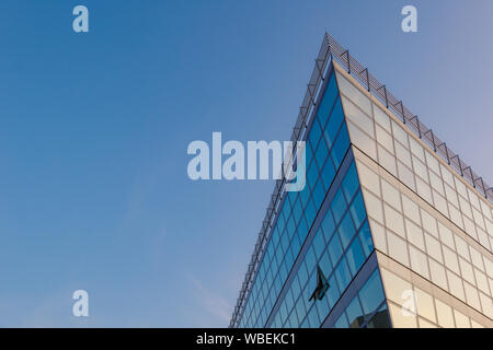 Close up outdoor view of exterior detail grid frame with reflected glass panel facade at the corner of building against blue and twilight sky. - Stock Photo