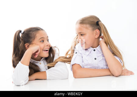 Making new friends in school. Happy small friends talking during class. Little school friends smiling to each other isolated on white. Adorable girl friends enjoying good friendship relations. - Stock Photo