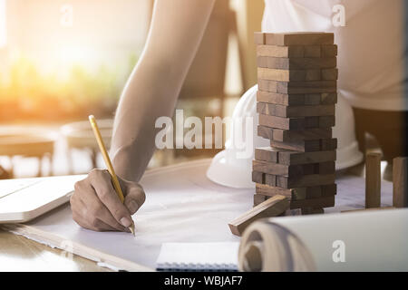 Projecting with pencil on the big urban drawings. Town planning and wood tower model for a architecture,architect working with vintage tone. - Stock Photo