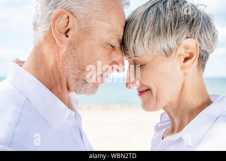 side view of smiling senior couple touching foreheads with closed eyes at beach - Stock Photo