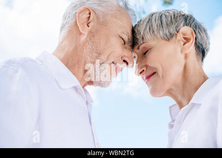 smiling senior couple touching foreheads with closed eyes under blue sky - Stock Photo